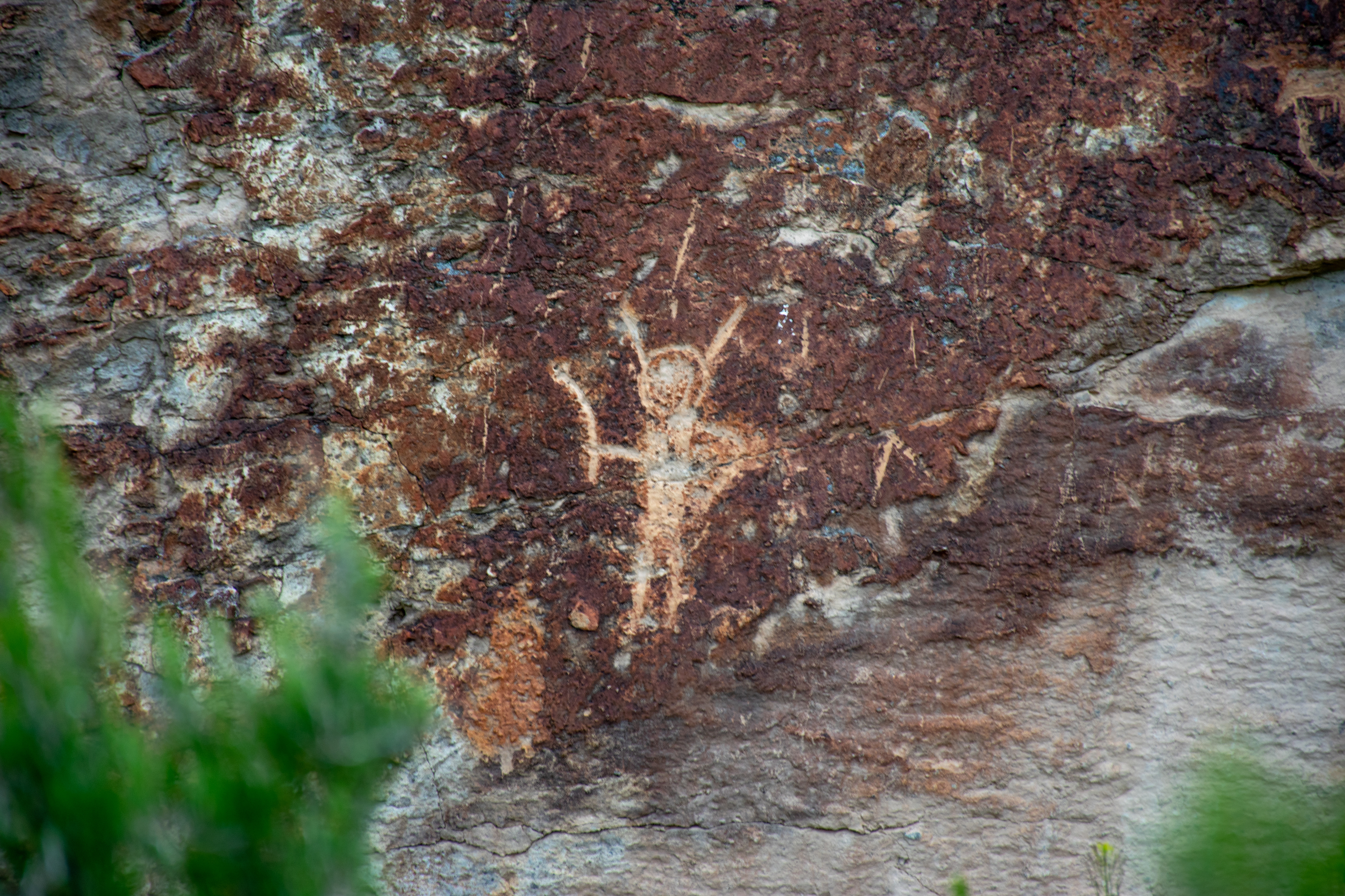 A humanoid figure drawing on a rock wall