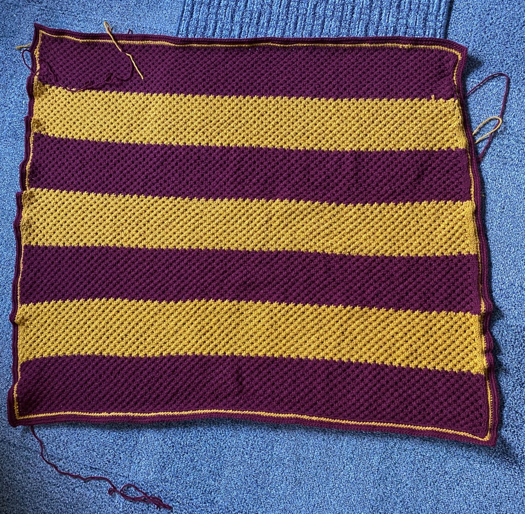 An image of the completed blanket with alternating stripe colors to match Gryffindor house colors and a crocheted borders. Various yarn tails are sticking out around the project