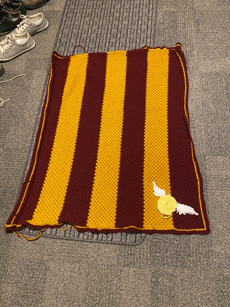 The striped baby blanket with the stripes running vertically, the snitch is still in the bottom right corner but now it has one wing on each side of it