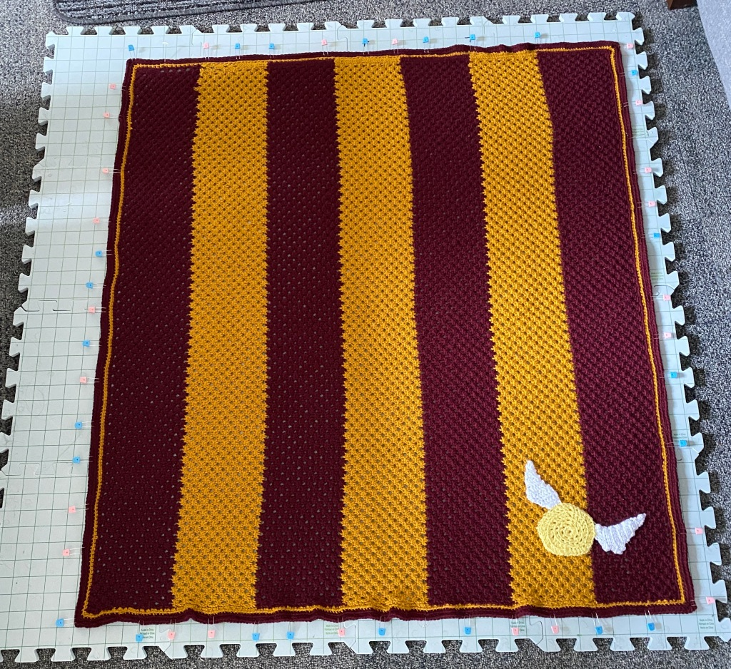 The finished baby blanket with the snitch attached on the bottom right corner, the blanket is placed on foam blocking boards and pins are holding the blanket into a flat rectangular shape
