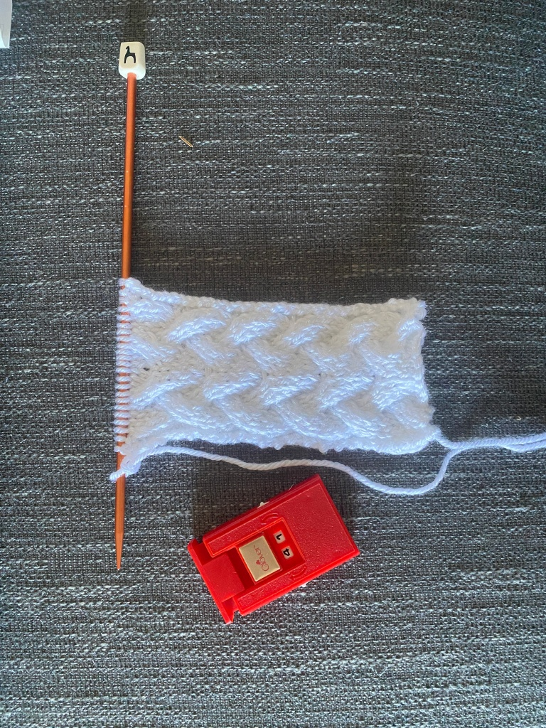 41 rows are shown to have been knitted on the red counter lying next to the partially started white braided cable rectangle.