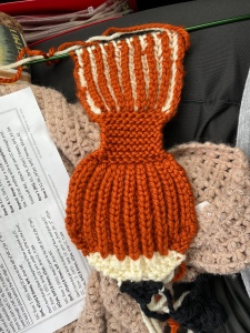 The beginning of a fox head and a short length of the scarf still on a long green double pointed needle